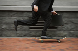 Business executive riding on skateboard