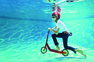teenager pushing a scooter underwater
